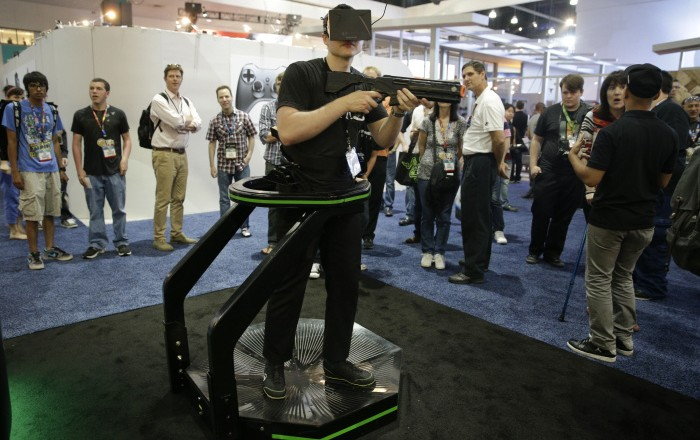 A gamer demonstrates on the Virtuix Omni virtual reality treadmill at the Electronic Entertainment Expo on Tuesday, June 10, 2014, in Los Angeles. (AP Photo/Jae C. Hong)