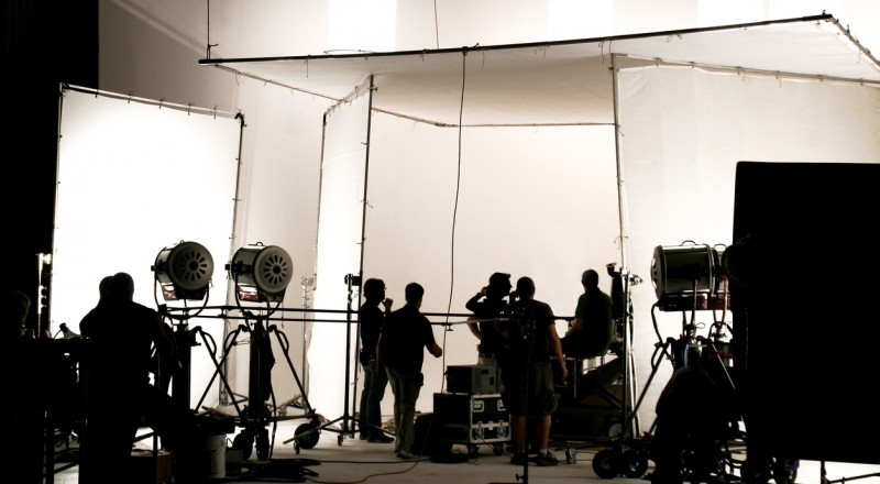 Silhouette of a production in progress on a white stage.